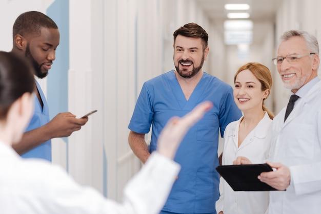 Świętujemy jeszcze jedno uratowane życie. zadowoleni rozbawieni, biegli lekarze, którzy spędzają wolny czas w szpitalu i wyrażają zachwyt, dzieląc się pozytywnymi wiadomościami