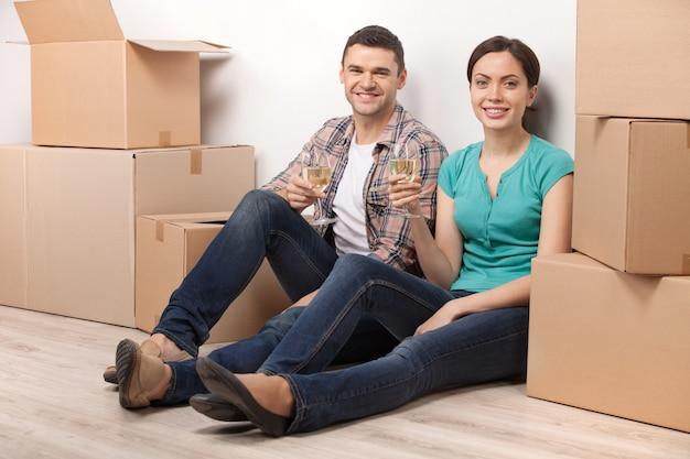 Świętujemy nowe mieszkanie. piękna młoda kochająca para siedzi na podłodze i trzyma kieliszki z winem, podczas gdy wokół nich leżą kartony