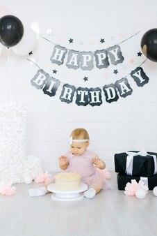 Świętujemy pierwsze urodziny małej dziewczynki. dziecko siedzi przy torcie w świątecznej strefie zdjęć
