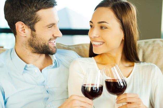 Świętujemy rocznicę. piękna młoda kochająca para siedzi blisko siebie i pije czerwone wino
