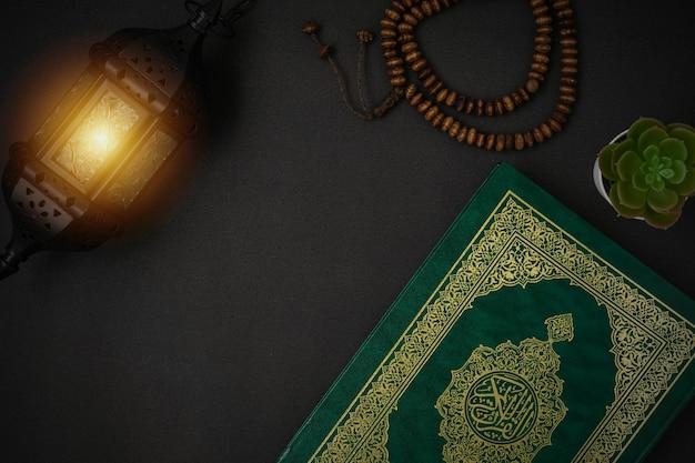 Święty al koran z napisanym kaligrafią arabską znaczeniem al koran i koralikami różańca na czarnym tle z kopią miejsca