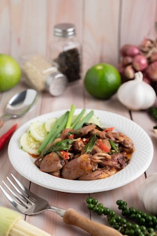 Święty bazyli smażony ryż z sercem kurczaka na białej drewnianej podłodze.