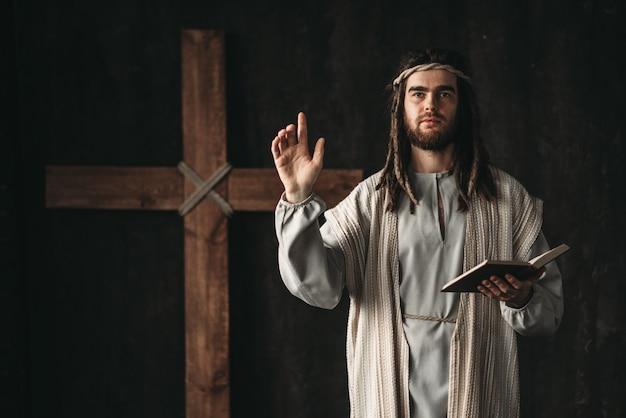 Święty jezus chrystus modląc się z biblijnymi w rękach, krzyż na czarnym tle