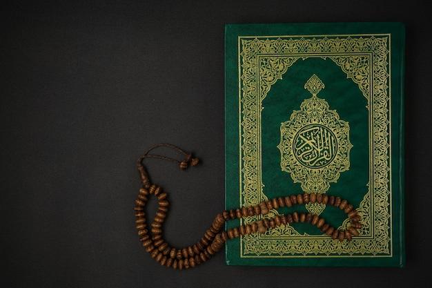 Święty koran al z napisem kaligrafii arabskiej, co oznacza koran al i różaniec na czarnym tle