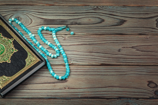 Święty koran z koralikami na drewnianej powierzchni