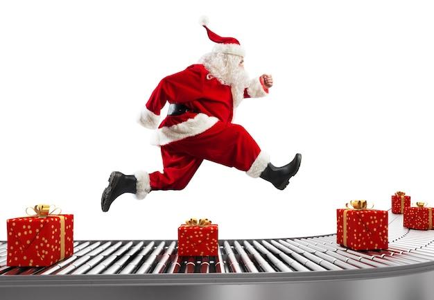 Święty mikołaj biegnie na taśmociągu, aby zorganizować dostawy w okresie świątecznym
