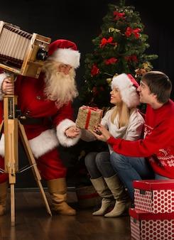 Święty mikołaj bierze obrazek para z starą drewnianą kamerą blisko choinki w domu
