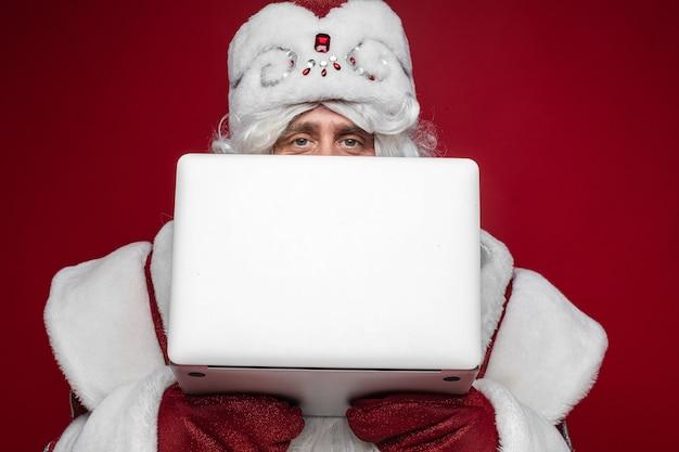 Święty mikołaj chowając się za laptopem