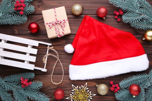 Święty mikołaj czerwony kapelusz i prezenty na szarym tle. świąteczne ozdoby.