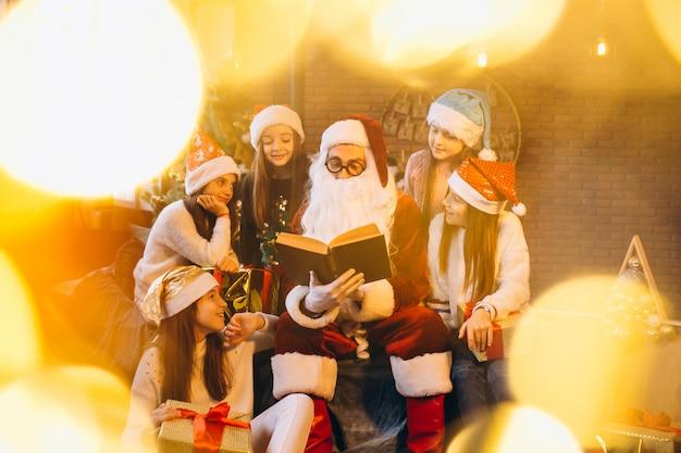 Święty mikołaj czyta książkę grupa dzieciaki