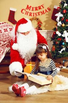 Święty mikołaj czyta książkę z małą słodką dziewczynką w pobliżu kominka i choinki w domu