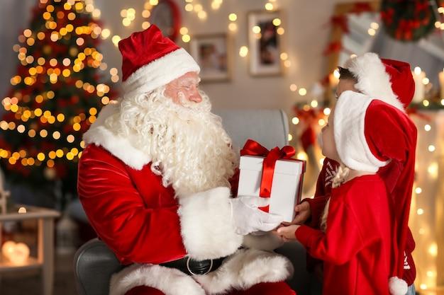 Święty mikołaj daje prezent dzieciom w pokoju z pięknymi dekoracjami świątecznymi