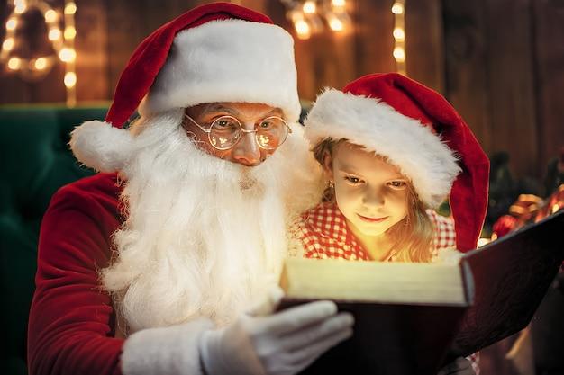 Święty mikołaj daje prezent małej uroczej dziewczynie