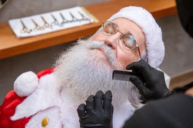 Święty mikołaj do golenia w salonie fryzjerskim. przygotowanie do bożego narodzenia. upiększanie na święta. brodaty. cięcie.