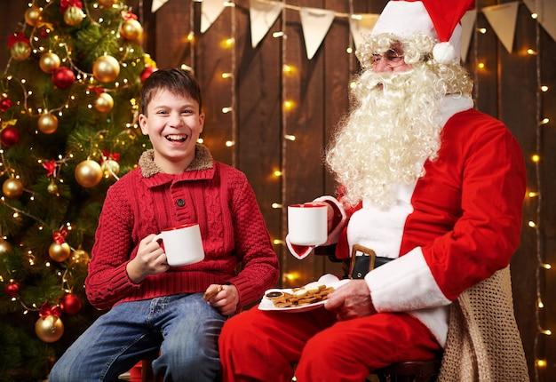 Święty mikołaj i chłopiec dziecko, picie herbaty, jedzenie ciasteczek, mówienie