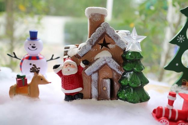 Święty mikołaj i drewniany dom z choinką, reniferem niosącym czerwone pudełko i bałwanem.
