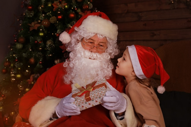 Święty mikołaj i dziecko w domu. prezent na boże narodzenie. koncepcja rodzinne wakacje.