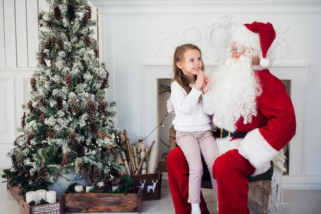 Święty mikołaj i dziecko w domu w pobliżu choinki