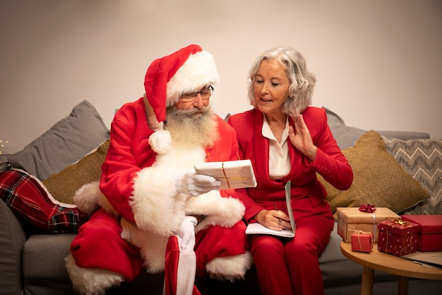 Święty mikołaj i kobieta przygotowuje prezenty świąteczne