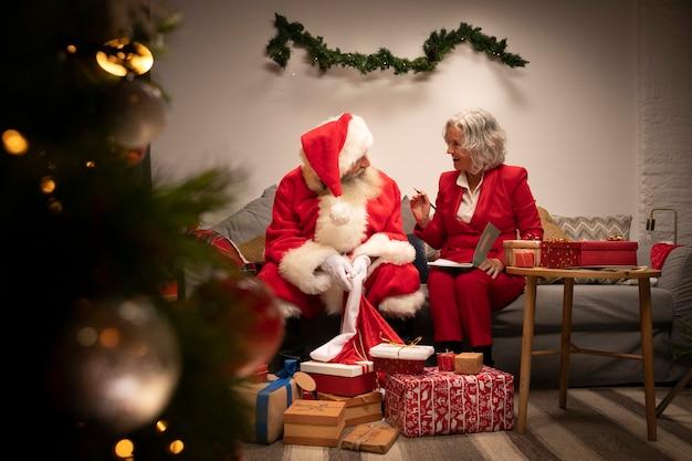 Święty mikołaj i kobieta przygotowywający dla bożych narodzeń