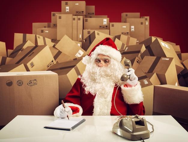Święty mikołaj jest gotowy, aby wysłuchać całej kolejności prezentów na wigilię bożego narodzenia.