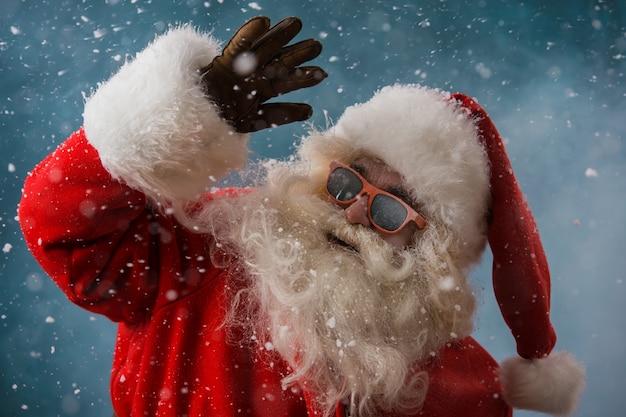 Święty mikołaj jest ubranym okulary przeciwsłonecznych outdoors przy biegunem północnym