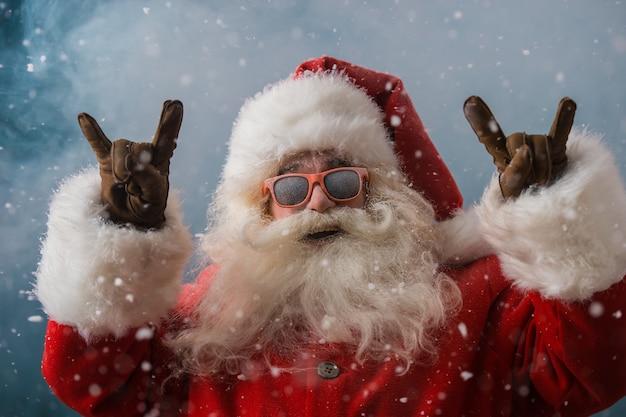 Święty mikołaj jest ubranym okulary przeciwsłonecznych tanczy outdoors przy biegunem północnym