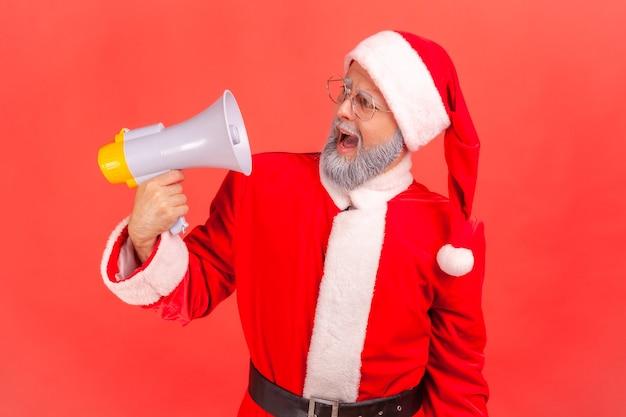 Święty mikołaj krzyczy głośno, ma zły wyraz twarzy, trzymając megafon.
