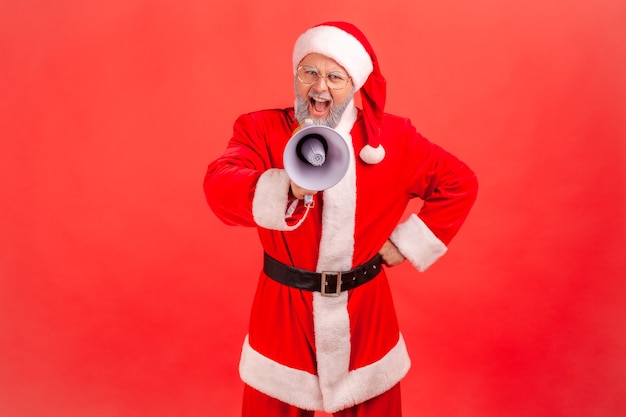 Święty mikołaj krzyczy trzymając megafon głośnikowy, bawiąc się z okazji ferii zimowych.