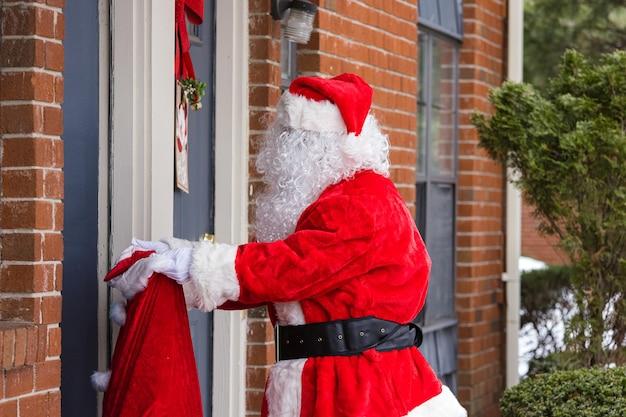 Święty mikołaj niosący dużą torbę dostawy prezentów świątecznych na zewnątrz, w pobliżu domu