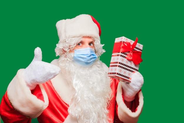 Święty mikołaj nosi papierową maskę na twarz z powodu covid-19. koronawirus jest niebezpieczny i występuje na całym świecie. bądź bezpieczny i noś maskę. odosobniony. miejsce na tekst.