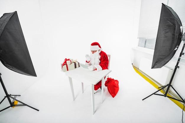 Święty mikołaj obsiadanie przy stołem w fotografii studiu