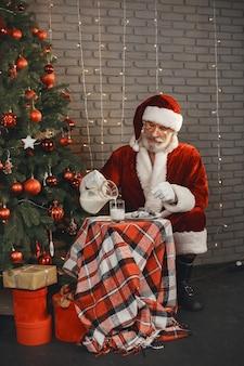 Święty mikołaj odpoczywa przy choince. dekoracja domowa. prezent dla mikołaja.