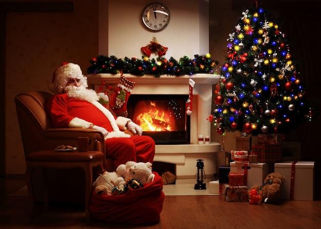 Święty mikołaj odpoczywa w wygodnym fotelu przy kominku w domu