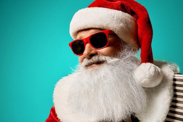 Święty mikołaj ono uśmiecha się i pozuje w czerwonych okularach przeciwsłonecznych
