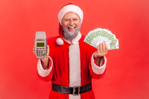 Święty mikołaj patrząc na kamery z uśmiechem, trzymając banknoty terminala i euro.
