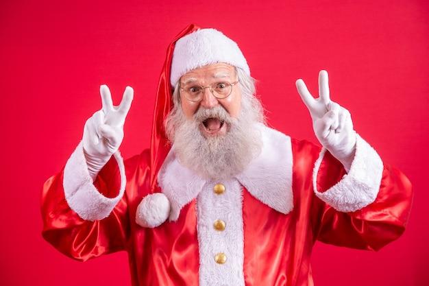 Święty mikołaj patrząc w kamerę. święta nadchodzą. wesołych świąt. pokój. znak v.