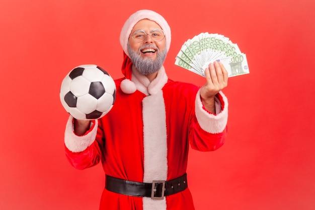 Święty mikołaj patrzący na kamerę z podekscytowaniem, trzymający piłkę nożną i pieniądze, obstawianie i wygrywanie.