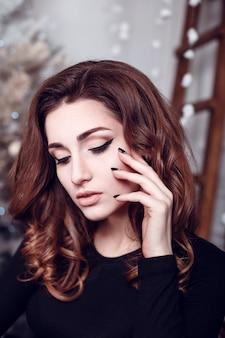 Święty mikołaj piękny uśmiechnięty kobieta model. makijaż. zdrowa fryzura długa. elegancka dama w czarnej sukni nad choinką zaświeca tło. szczęśliwego nowego roku