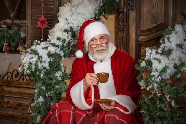 Święty mikołaj pije gorącą herbatę lub kawę.