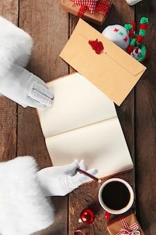 Święty mikołaj pisze w notatniku na drewnianej powierzchni
