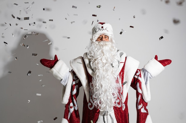 Święty mikołaj pod świątecznym konfetti przedstawiającym gest powitalny
