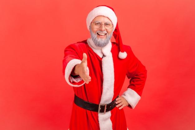 Święty mikołaj podający rękę do uścisku dłoni, witający ludzi na przyjęciu bożonarodzeniowym.