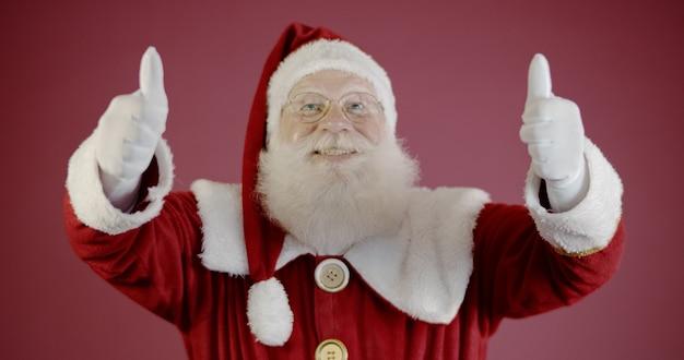 Święty mikołaj pokazując kciuk do góry. święty mikołaj z prawdziwą brodą i wielkim uśmiechem daje kciuk w górę.