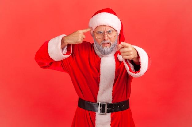 Święty mikołaj pokazuje głupi gest wskazujący palcem na ciebie patrząc na kamerę, obwiniając i szydząc.