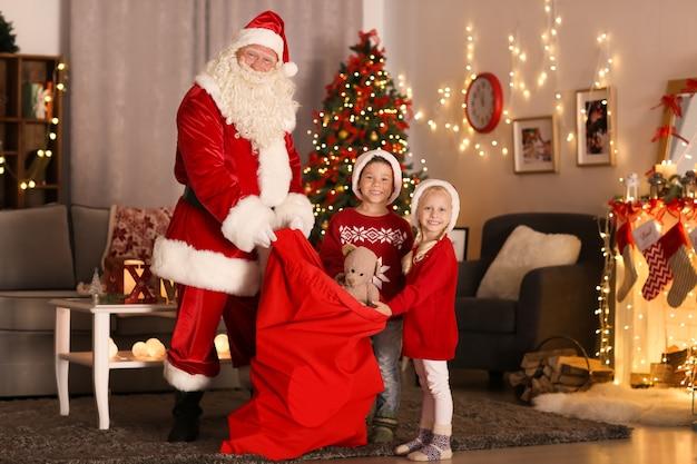 Święty mikołaj pokazuje prezenty uroczym dzieciom w pokoju z pięknymi dekoracjami świątecznymi
