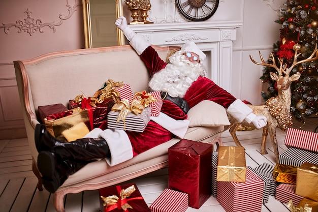 Święty mikołaj położył się, aby odpocząć na sofie z bukietem prezentów przy kominku i choince. wesołych świąt, wesołych świąt koncepcja