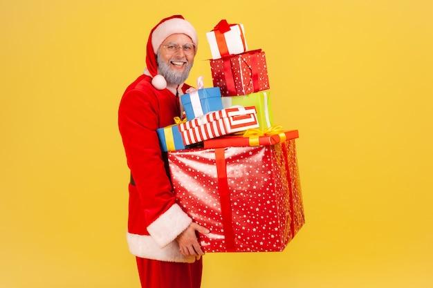 Święty mikołaj pozuje ze stosem prezentów w ręce, będąc gotowym do świętowania bożego narodzenia.
