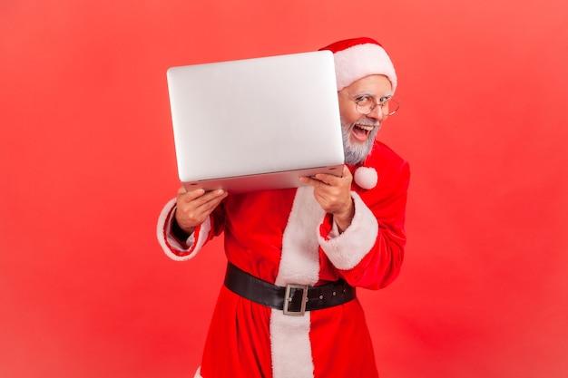 Święty mikołaj pozuje zerkając z laptopa, śmiejąc się radośnie, ferie zimowe.