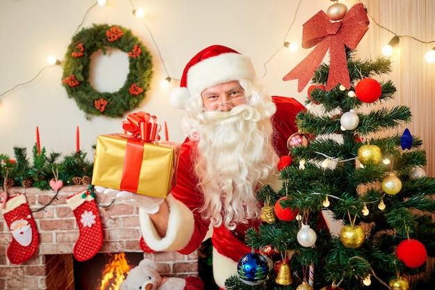 Święty mikołaj przy choinką z prezentem w jej ręce ono uśmiecha się przy bożymi narodzeniami, nowy rok.